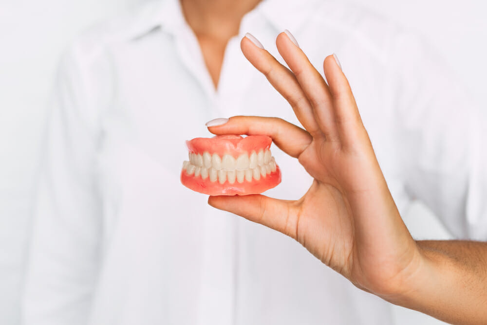 Person holding set of dentures